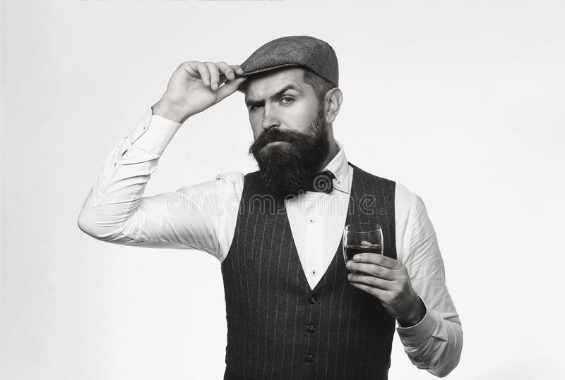 有胡子的人佩带的衣服和饮用的威士忌酒,白兰地酒,科涅克白兰地 有胡子和杯威士忌酒 斟酒服务员品尝昂贵 库存照片