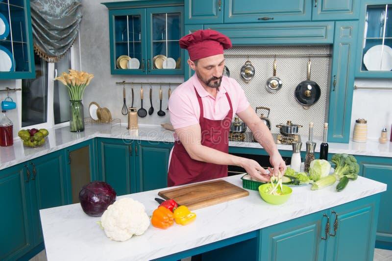 有胡子的人切口菜和烹调沙拉在厨房内部 厨师制服的人在家烹调菜厨房的 库存照片