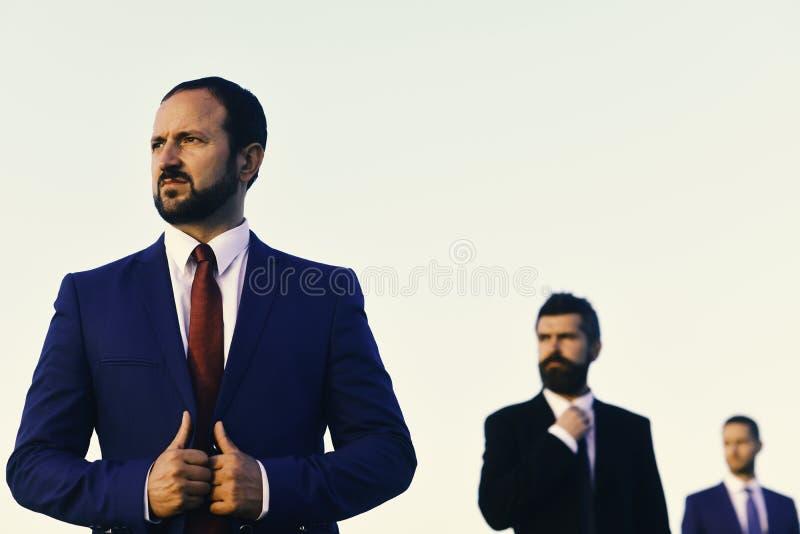 有胡子的人和严肃的面孔看得在旁边 商人接触夹克 经理佩带聪明的衣服和领带 免版税库存照片