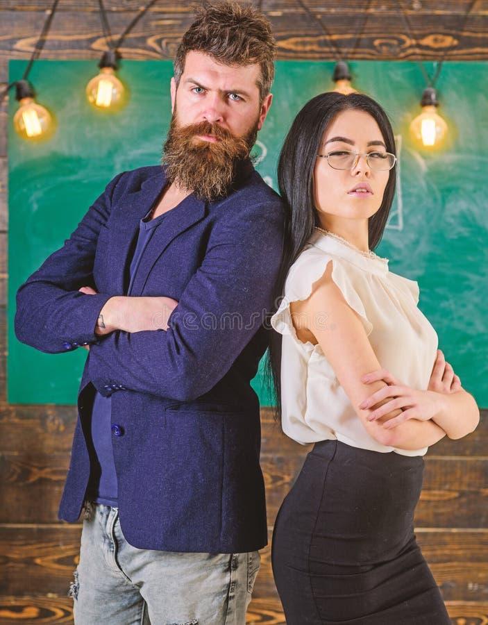 有胡子的人和老师站立支持,在背景的黑板 学校职员概念 老师,男校长 免版税库存图片