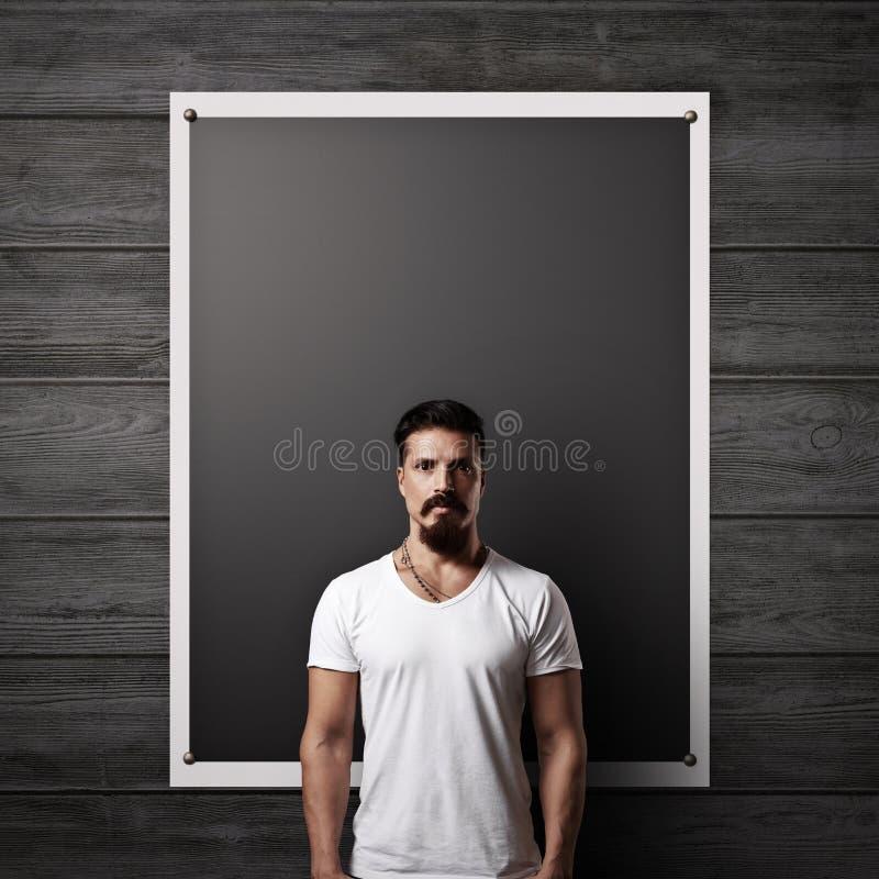 有胡子的人和黑海报在木墙壁上 图库摄影
