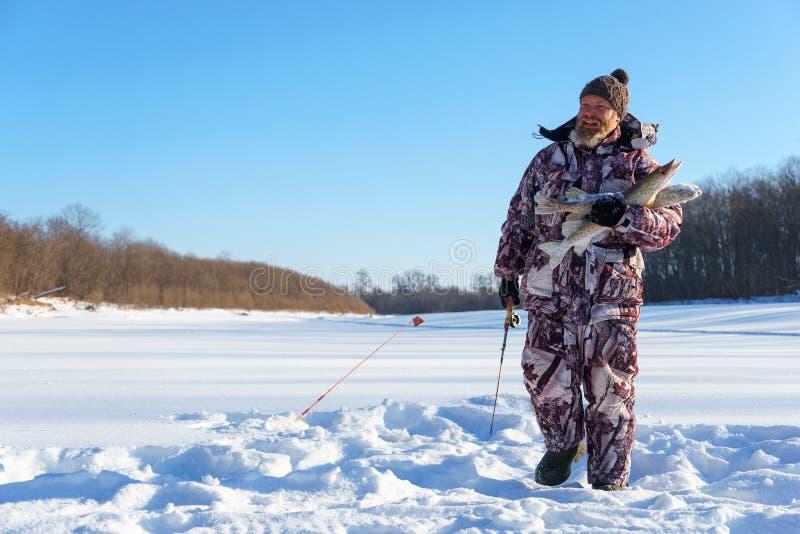 有胡子的人在成功的冬天渔以后拿着结冰的鱼冷的晴天 免版税图库摄影
