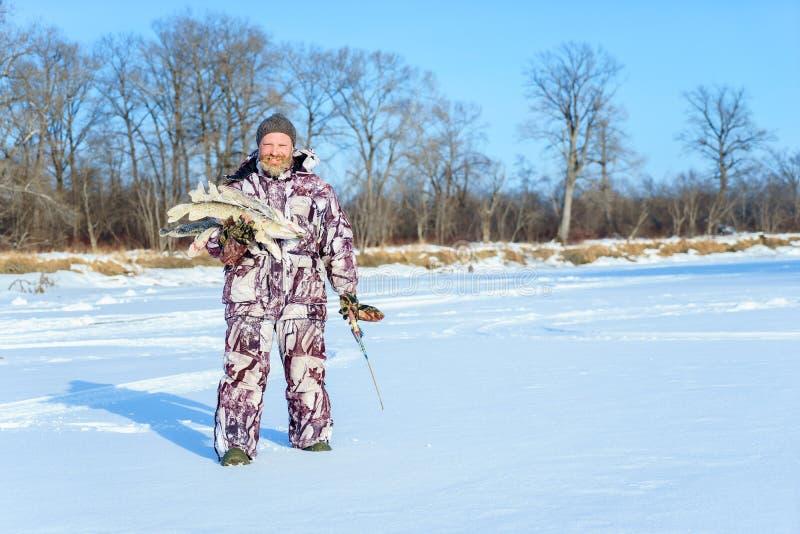 有胡子的人在成功的冬天渔以后拿着结冰的鱼冷的晴天 免版税库存照片