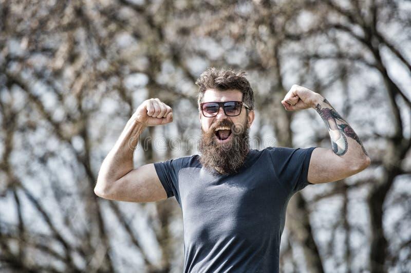 二头肌 阳刚之气概念 有长的胡子的人看起来精力充沛和快乐 库存图片