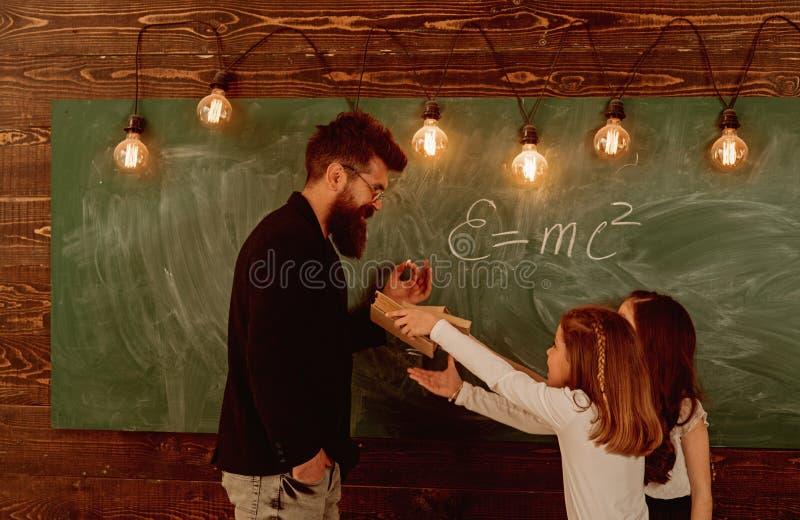 有胡子的人在正式衣服教女小学生物理 老师和女孩学生在黑板附近的教室 免版税库存照片
