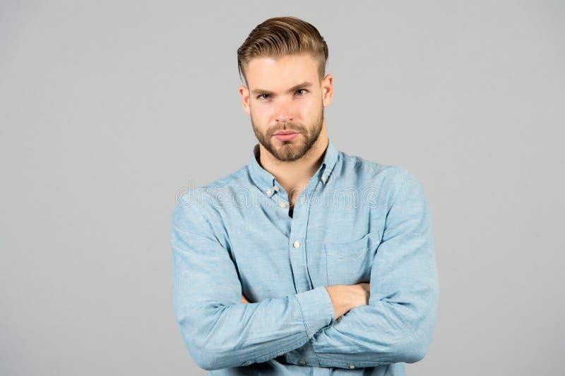 有胡子的人在灰色背景保持胳膊横渡 有严肃的面孔的强壮男子 疲倦在每天工作以后 办公室着装条例 库存图片
