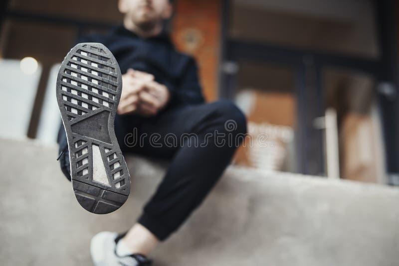 有胡子的人坐具体步鄹和举的腿 免版税图库摄影