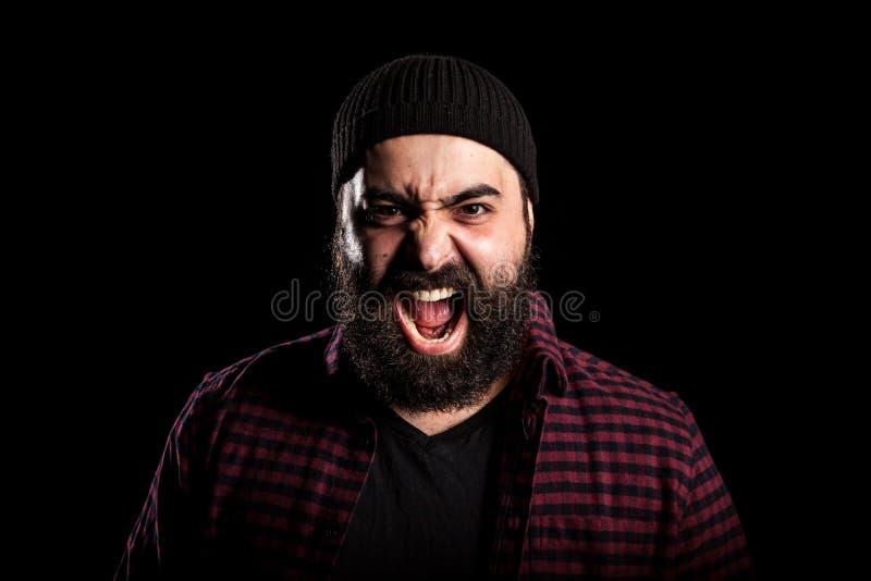 有胡子的人尖叫在黑背景的愤怒 免版税库存照片