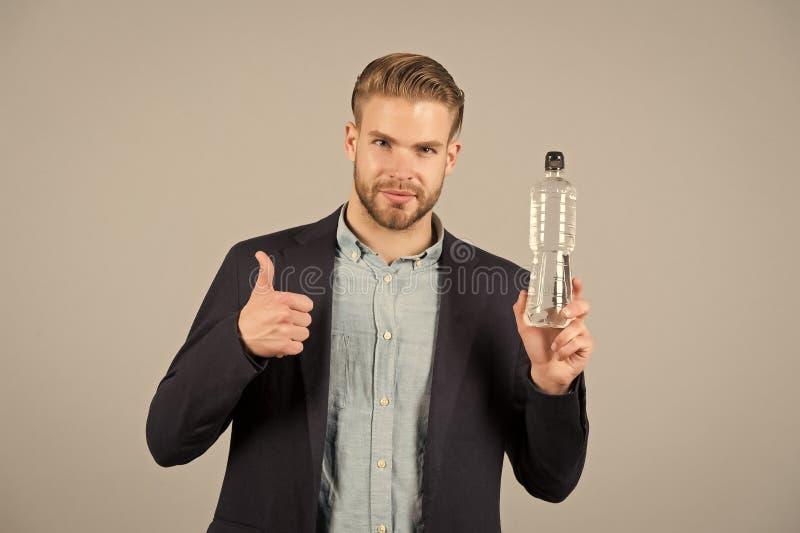 有胡子的人展示赞许到瓶水 与胡子的渴商人在蓝色衬衣和外套 干渴和 免版税库存图片