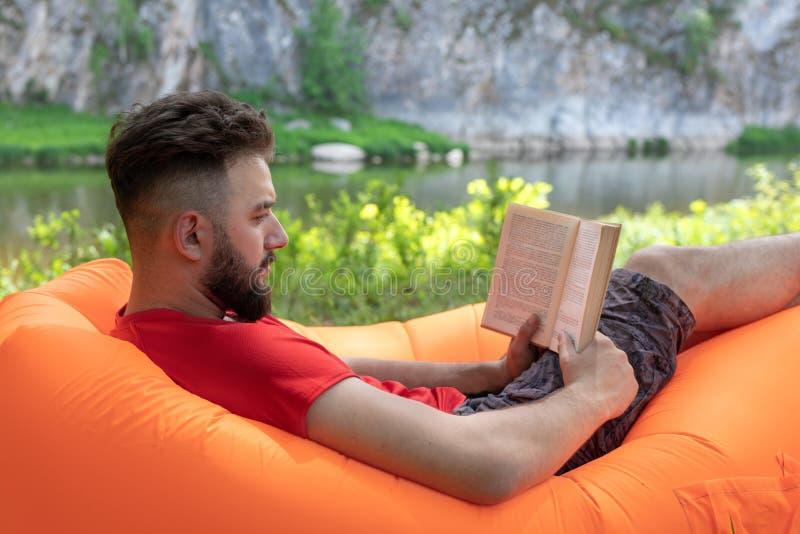 有胡子的人或人在橙色可膨胀的空气懒人,室外的沙发读说谎一本的书 图库摄影