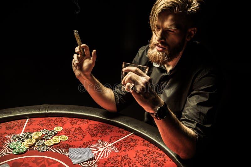 有胡子的人抽烟的雪茄和饮用的威士忌酒,当打扑克时 库存图片