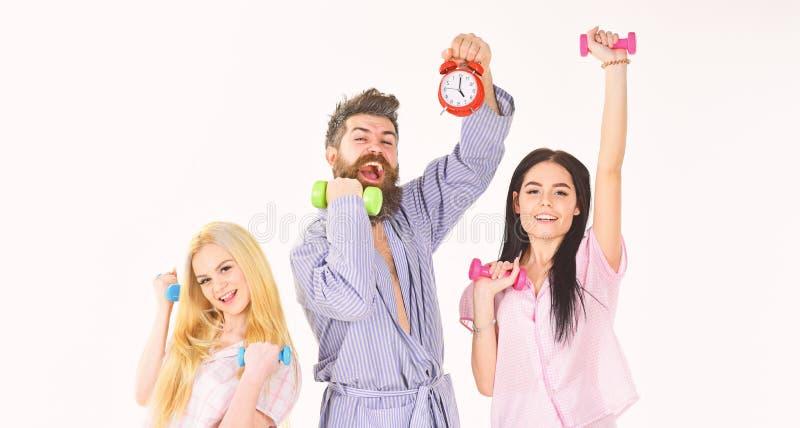 有胡子的人拿着闹钟 健身生活方式概念 教练员,强壮男子与可爱的女孩做早晨锻炼 图库摄影