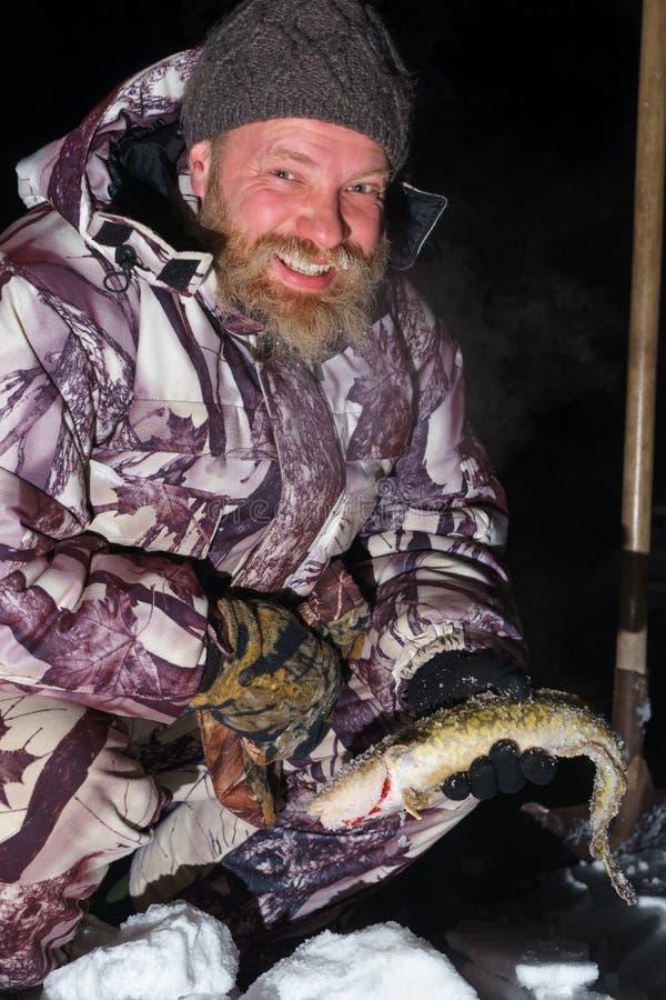 有胡子的人拿着鱼并且在黑暗的冬天晚上微笑着 免版税库存图片