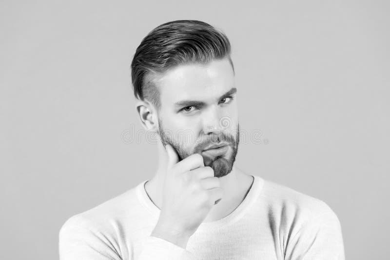 有胡子的人接触胡子用手 有时髦的头发和健康年轻皮肤的强壮男子 有不剃须的面孔和髭的人 免版税库存照片
