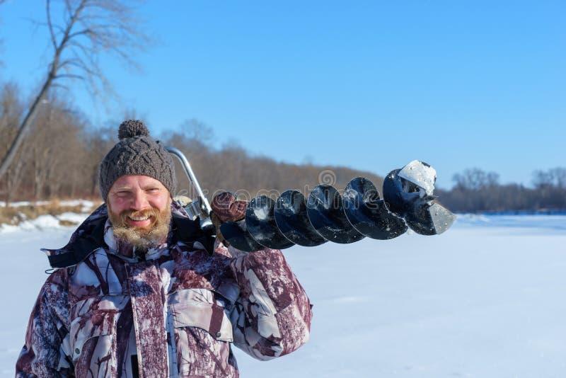 有胡子的人是钻冰孔由冬天渔的自动moto布尔人晴天在蓝天下 免版税库存照片