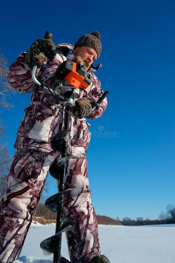 有胡子的人是钻冰孔由冬天渔的自动moto布尔人晴天在蓝天下 免版税库存图片
