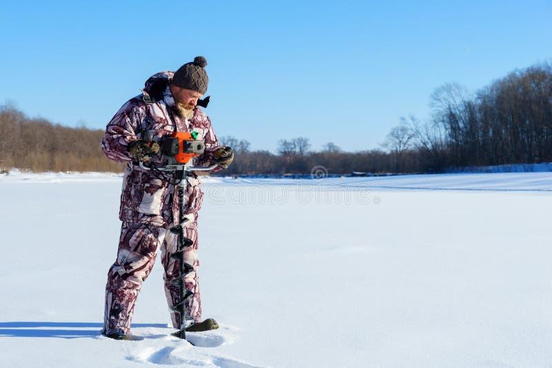有胡子的人是钻冰孔由冬天渔的自动moto布尔人晴天在蓝天下 库存图片