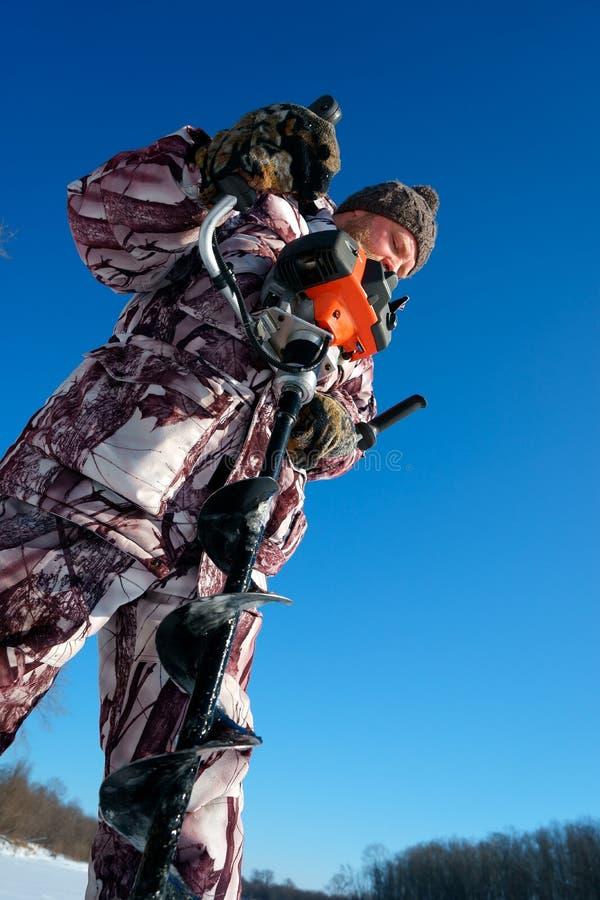 有胡子的人是钻冰孔由冬天渔的自动moto布尔人晴天在蓝天下 库存照片