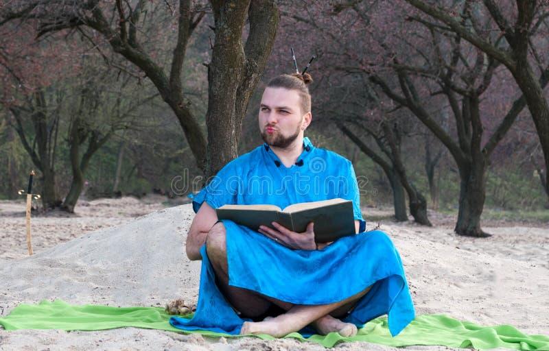 有胡子的人用在头的小圆面包在蓝色和服开会,拿着大书和看  免版税库存图片