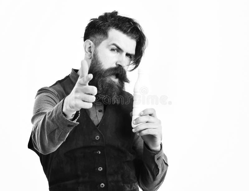 有胡子的人藏品瓶与严肃的面孔的牛乳气酒 免版税图库摄影