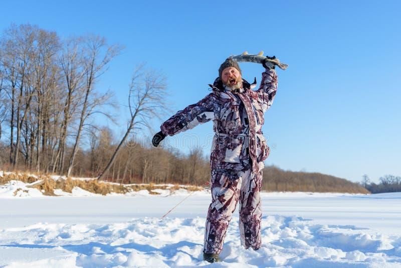 有胡子的人设法由冻鱼关上您在成功的冬天渔以后冷的晴天 库存图片