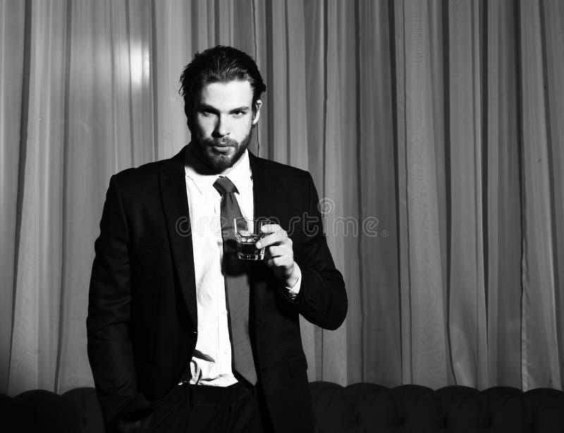 有胡子的人,与杯的商人威士忌酒 免版税库存图片