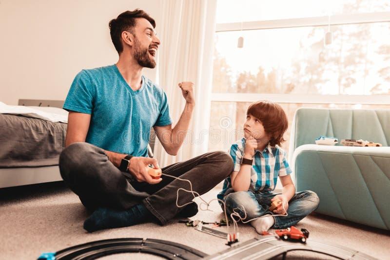 有胡子的使用与玩具种族路的父亲和儿子 免版税图库摄影