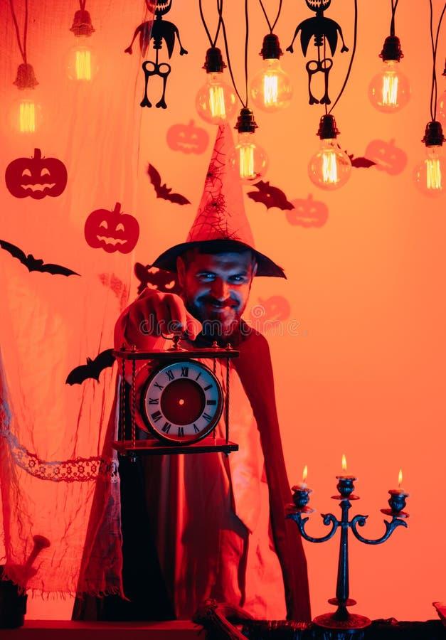 有胡子的可怕行家在巫婆帽子和格子衬衫 有微笑的万圣节人在黑暗的背景 巫术师,巫师 库存图片