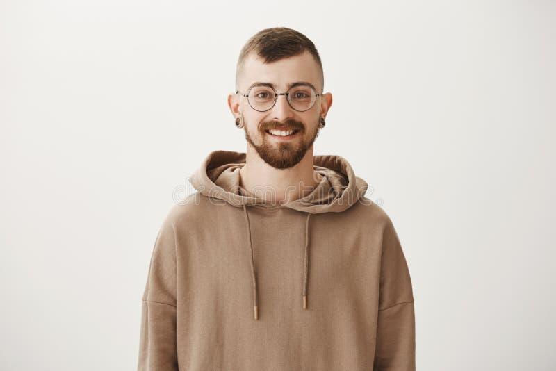 有胡子的可爱的时髦的供选择的人在时髦棕色有冠乌鸦和骨肉挖洞,快乐地微笑,是高兴的 库存图片
