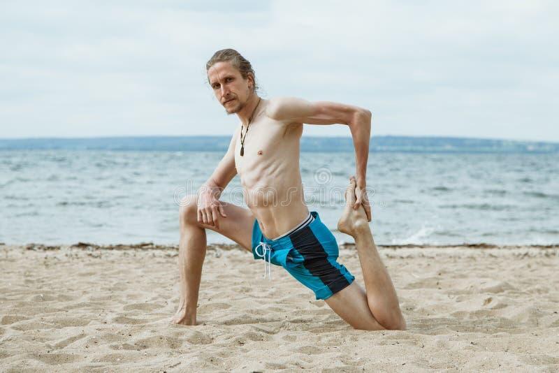 有胡子的吸引人年轻人实践瑜伽 免版税库存图片