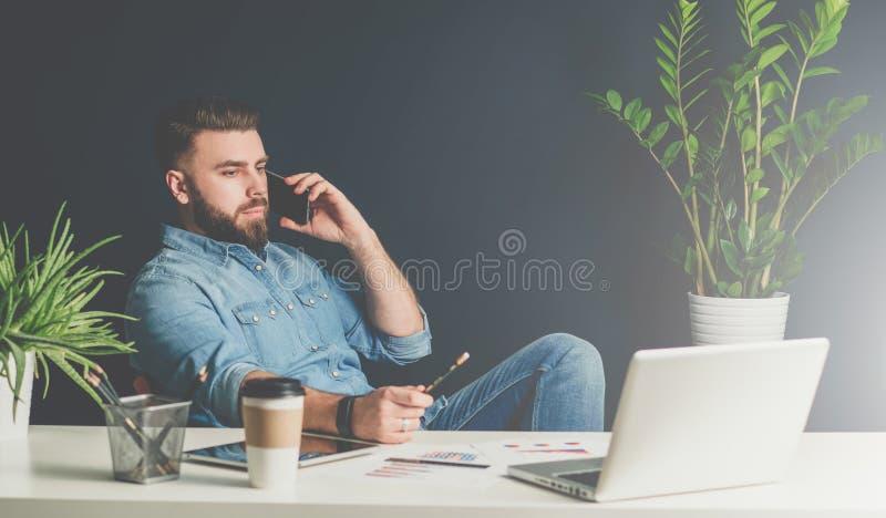 有胡子的商人在办公室坐在桌上,倾斜在椅子和谈话在手机,当看膝上型计算机时 免版税库存图片