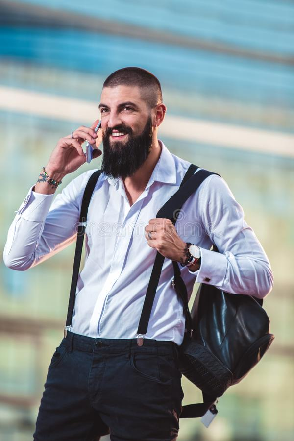 有胡子的商人谈话在他的电话户外 库存照片
