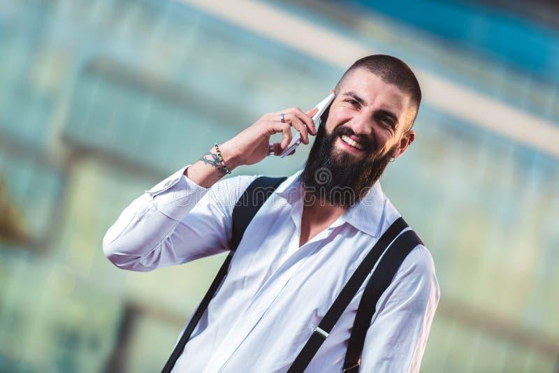 有胡子的商人谈话在他的电话户外 免版税库存照片