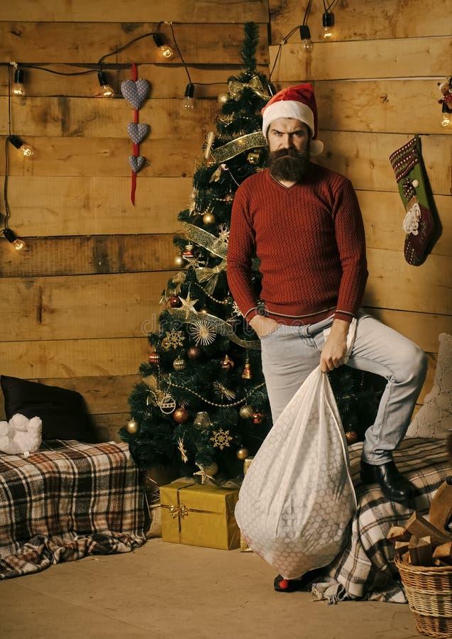 有胡子的圣诞节人在严肃的面孔当前袋装 免版税库存照片