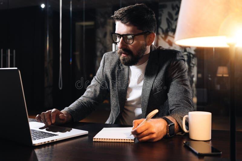 有胡子的工友由与灯和使用当代笔记本的木桌坐 商人举行笔和分析趋向 库存图片