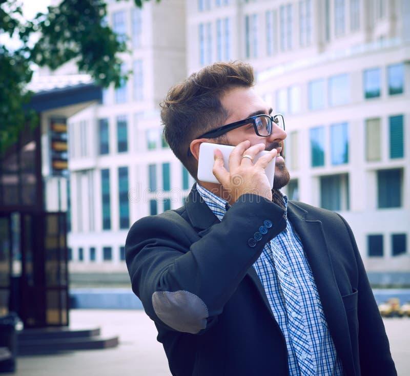 有胡子的年轻人在玻璃拿着咖啡杯和谈话在手机,当走户外时 免版税库存图片