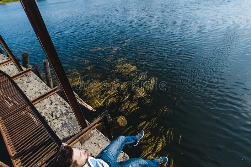 有胡子的年轻人 一次旅行向湖,一个被放弃的老水坝,温暖的晴朗的d 库存照片