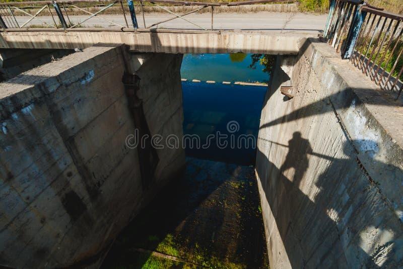 有胡子的年轻人 一次旅行向湖,一个被放弃的老水坝,温暖的晴朗的d 免版税库存照片