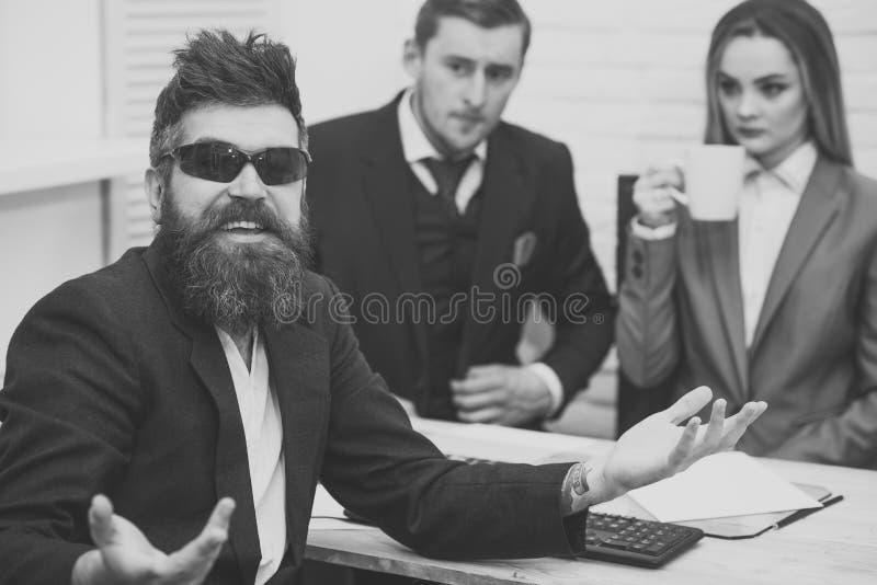 有胡子的微笑的人在太阳镜,上司,工友,背景的同事 为工作聘用的人愉快在办公室 库存图片