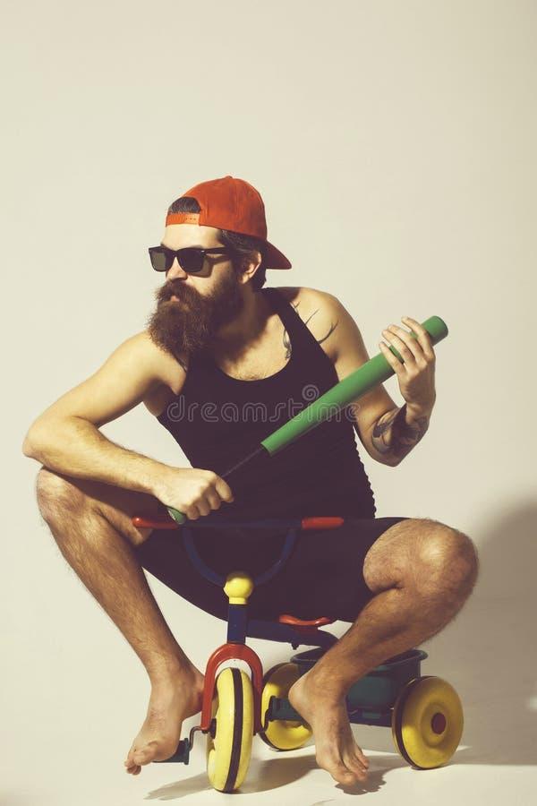 有胡子的恼怒的人拿着在自行车玩具的绿色棒球棒 免版税库存照片