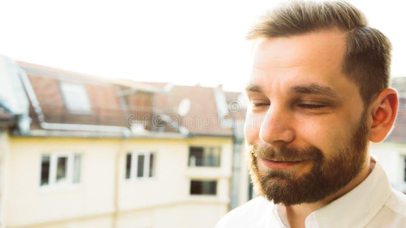有胡子的愉快的人有谈话的交谈在日落和白色衬衫 免版税库存照片