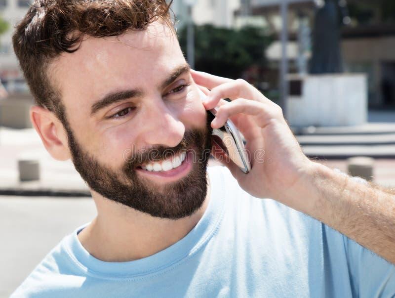 有胡子的愉快的白种人人在电话 库存照片