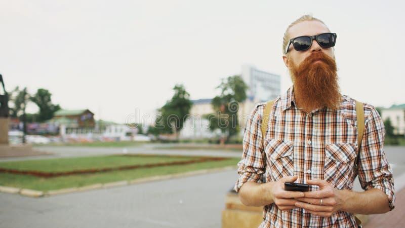 有胡子的旅游人在城市和使用丢失了智能手机在线地图发现正确的方向 免版税库存图片