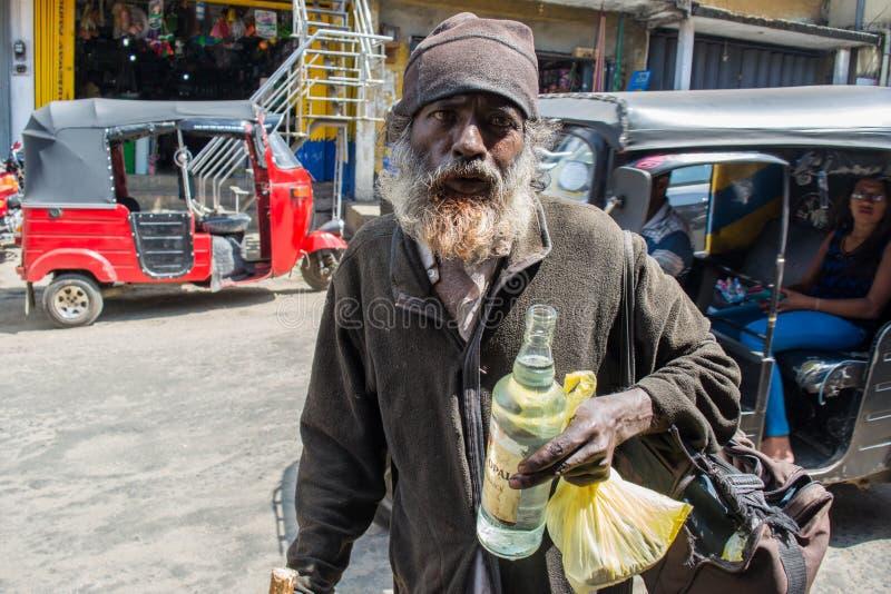 有胡子的无家可归的老色鬼和瓶在街道的手上 库存照片