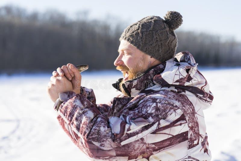 有胡子的欧洲人微笑着,当钓鱼与鱼的他在喂时 库存照片