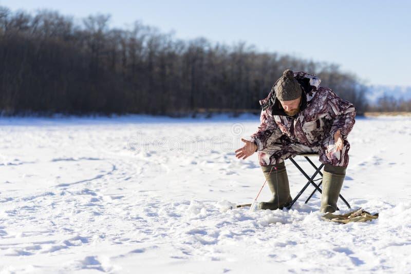 有胡子的欧洲人烦人,当钓鱼从冰孔时的他 库存照片