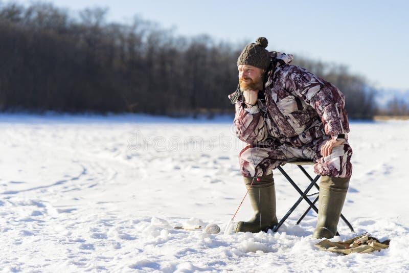 有胡子的欧洲人烦人,当钓鱼从冰孔时的他 免版税库存图片