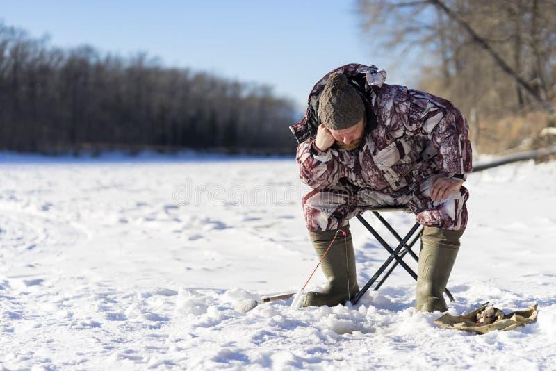 有胡子的欧洲人烦人,当钓鱼从冰孔时的他 免版税库存照片