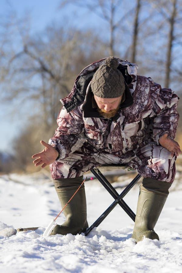 有胡子的欧洲人烦人,当钓鱼从冰孔的他时 免版税图库摄影