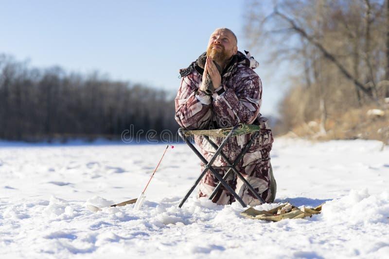 有胡子的欧洲哀伤的人祈祷,当获得失败的他冬天钓鱼时 免版税图库摄影